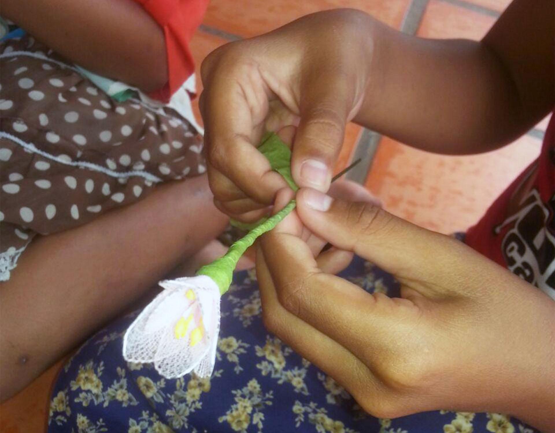 fiore tessuto mani bambina Cambogia Mani Tese 2018